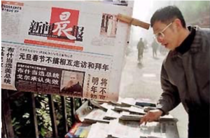 Man looks at newspapers with reports of George W. Bush's victory in U.S. presidential election at a newsstand in Shanghai, China, today. (FreedomForum.org)
